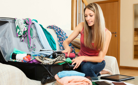 Serious girl trying to find room for all the things in trunk