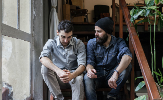 two hipster-looking guys talking on steps