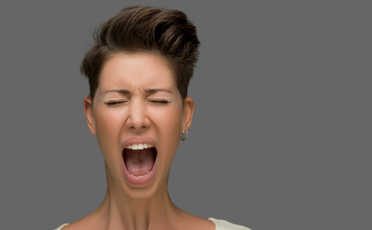 Shouting young woman, close up portrait (istock/ozgurdonmaz