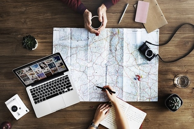 travel planning with laptop and map on a table