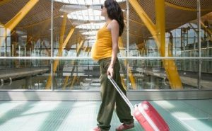 pregnant woman pulling a carryon through an airport terminal
