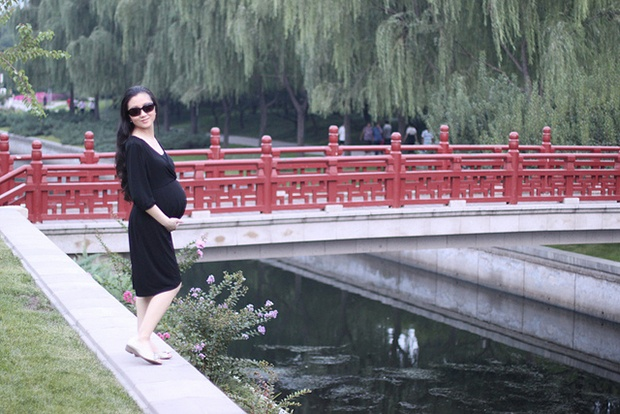 pregnant woman standing in a Japanese garden