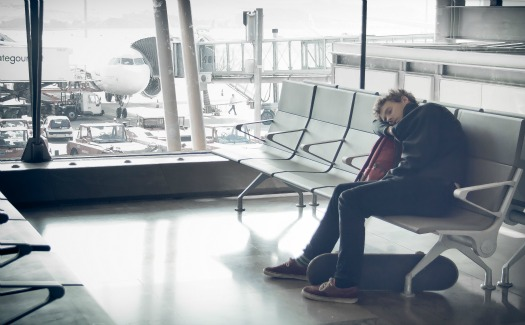 man dozing off sitting upright at airport