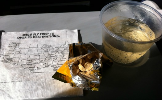 drink, peanuts, and cocktail napkin on seat tray