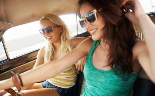 Young friends out for a drive together while laughing and smiling